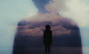 Donna di spalle in riflessione sul mare - Photo by La mente è meravigliosa